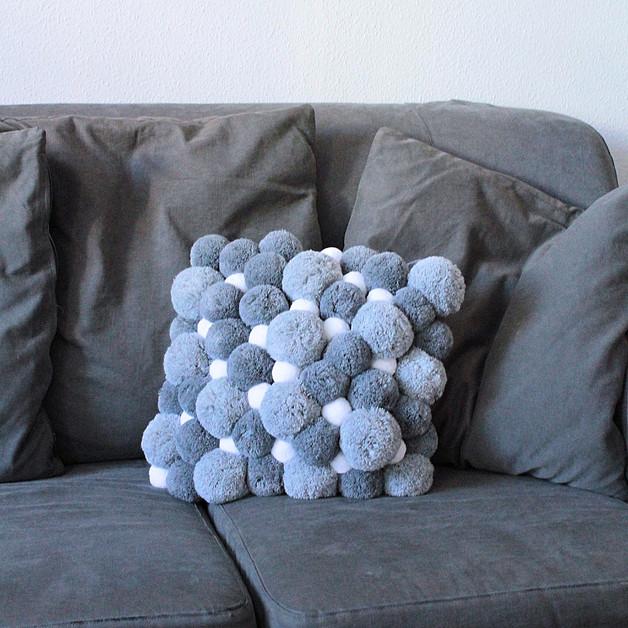 szara-poduszka-z-pomponów