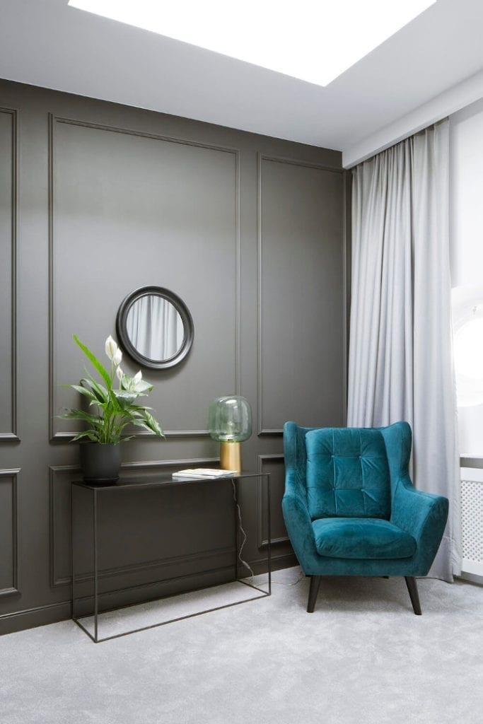 Ekskluzywne wnętrza czarna ściana biała ściana świetliki sufitowe niebieski fotel lampa rośliny we wnętrzu