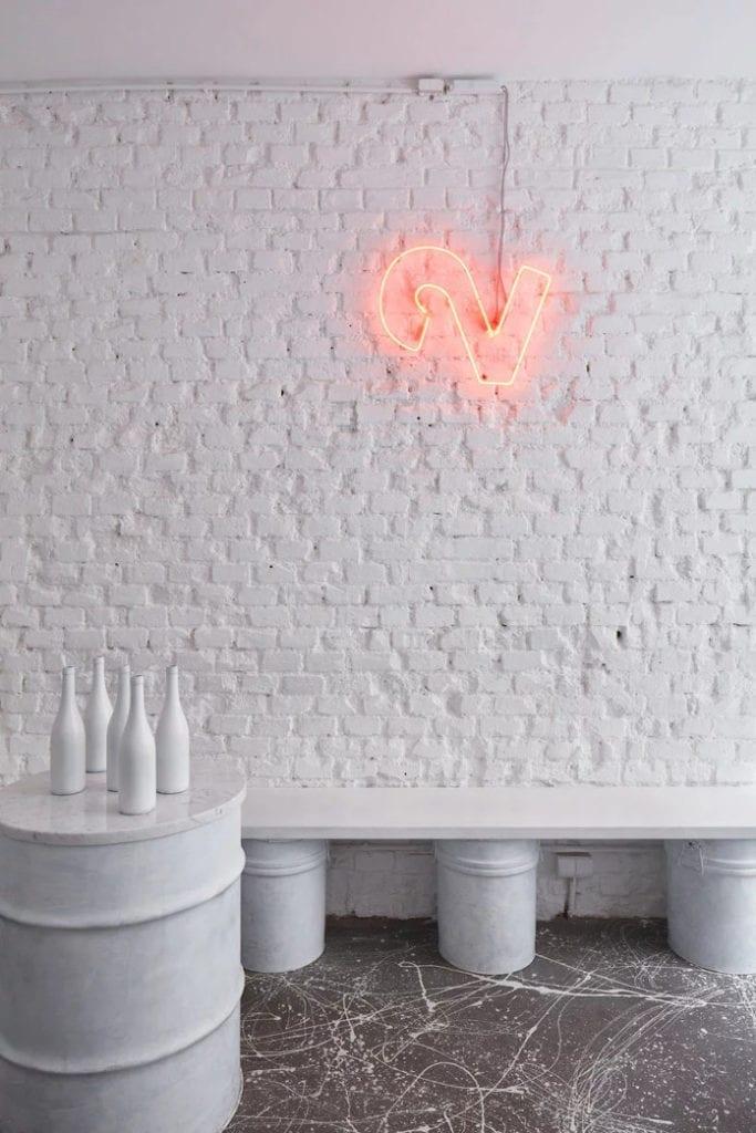 Czerwony neon białe ściany farba design beczka cegła