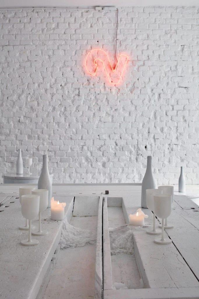 Czerwony neon białe ściany farba design cegła stół świeczki wino