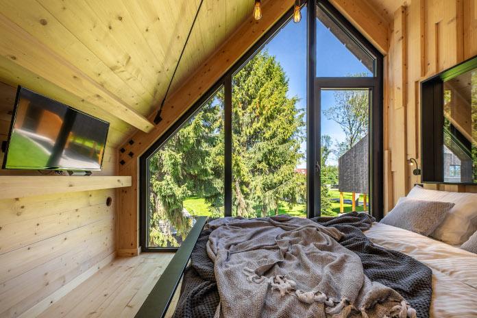 Szklana elewacja duże okna panoramiczna łóżko sypialnia telewizor pościel koc szary drewno