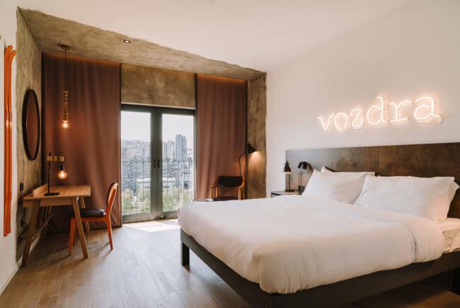 Nowy design aranżacja sypialni łóżko beton ściana biała neon biurko krzesło okno panoramiczne