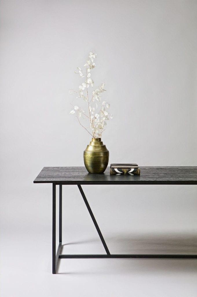 Nowoczesna klasyka we wnętrzu stolik czarny drewniany złoto dodatki