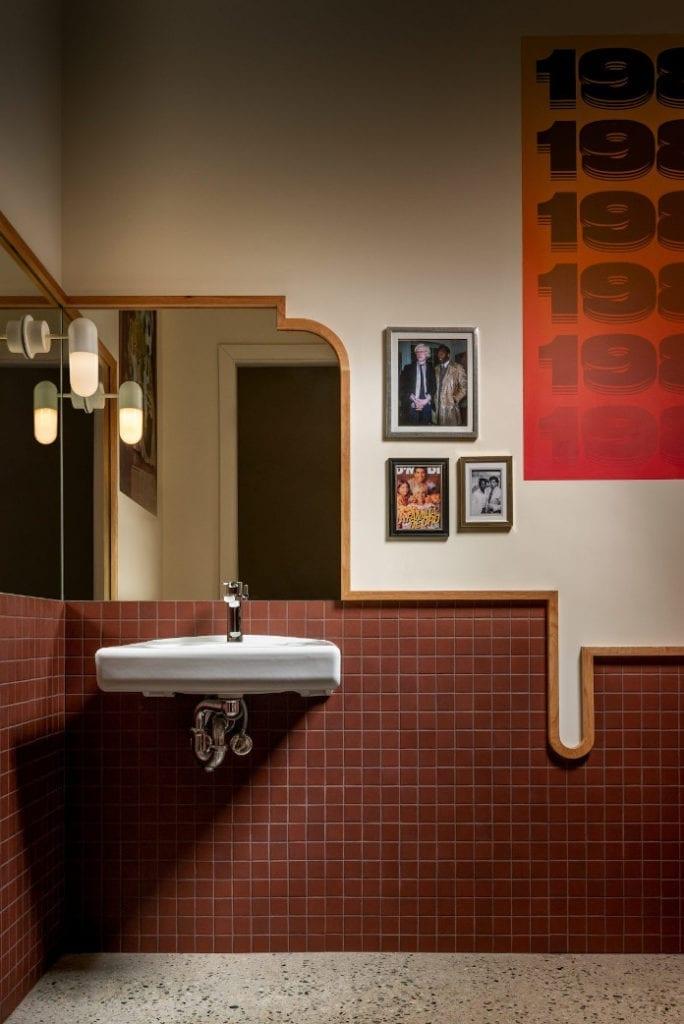 Klimatyczna restauracja łazienka płytki lustro lampa plakaty obrazki