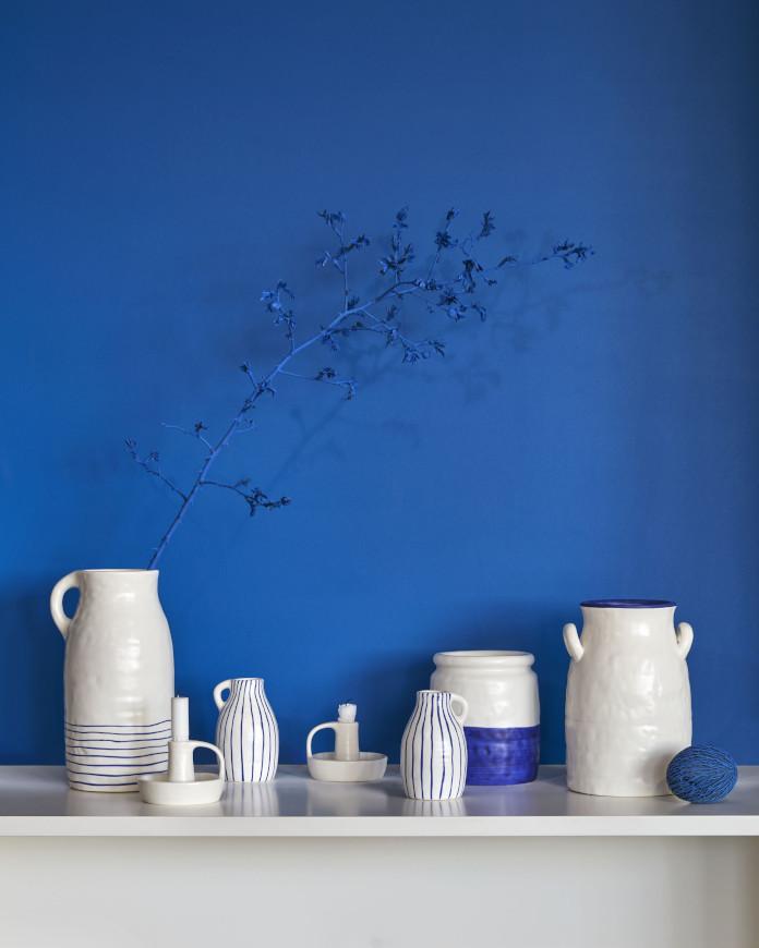 niebieska ściana biała porcelana wazon