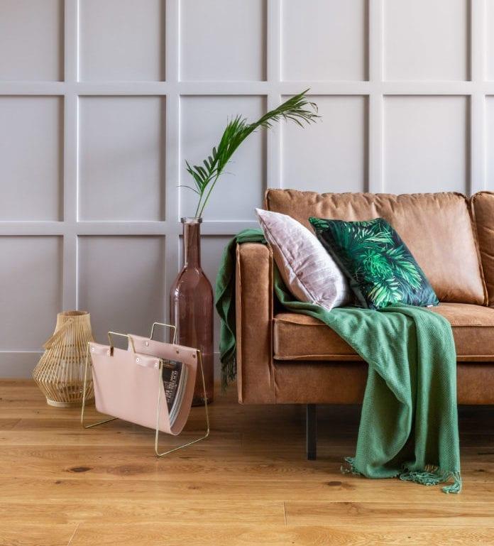 inspiracje zieleń we wnętrzu brązowa kanapa skórana koc palma