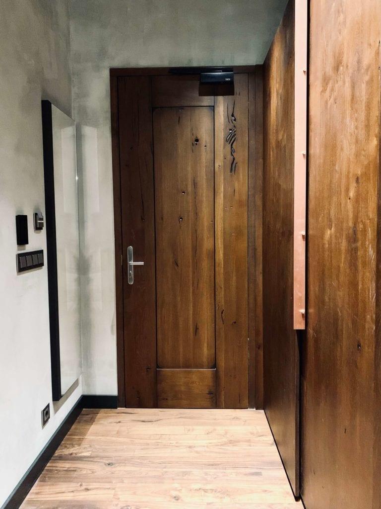 drewniane-drzwi-do-pokoju-w-hotelu-warszawa-betonowe-ściany-lustro-włoskie marki-drewniana-podłoga-szafa