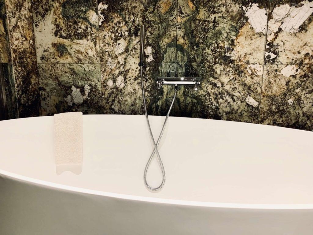 łazienka-w-pokoju-hotel-warszawa-ściany-kamienne-zielony-kamień-do-łazienek-inspiracje-luskusowe-wnętrze-wanna-wolnostojąca-chromowany-prysznic