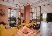 clay.warsaw w warszawie z różowymi ścianami w stylu vintage żółte sofy różowe pufy czarne krzesła podłoga w ktatkę