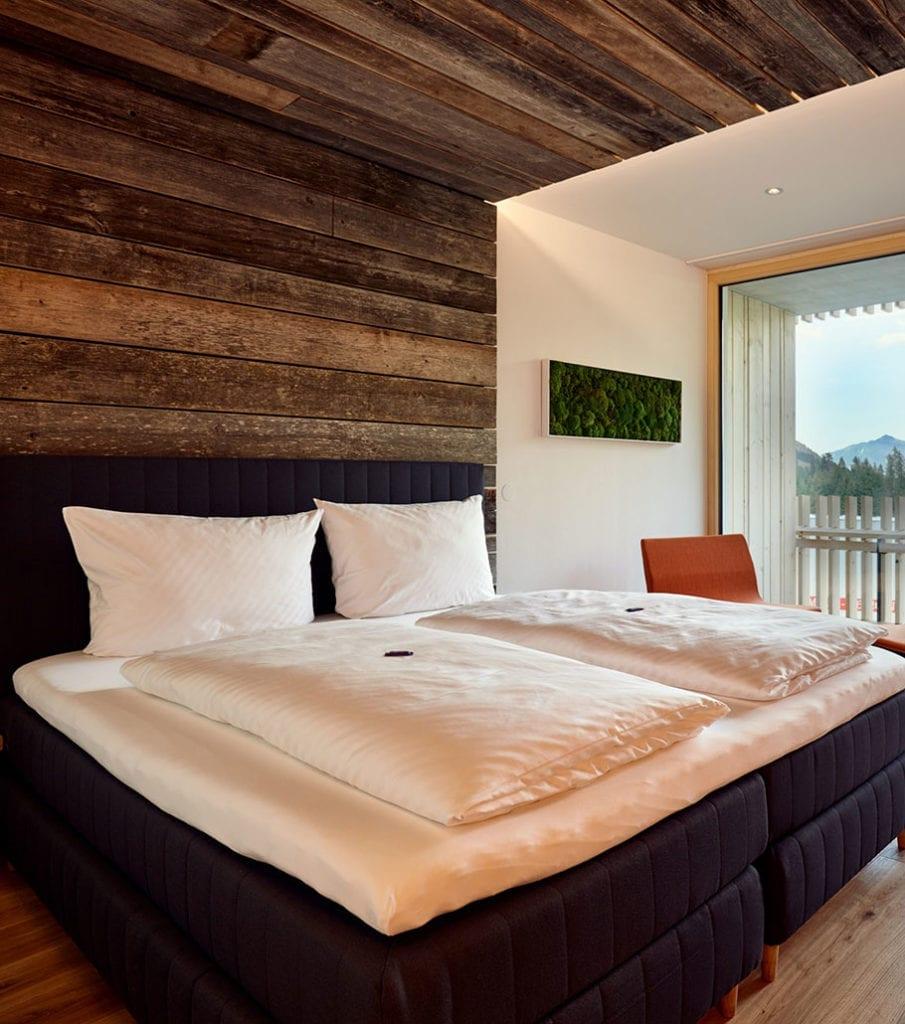 drewno-na-ścianie-w-pokoju-hotelu-w-austriackich-górach-sypialnia-duże-łóżko-z-poduszkamu-biała-pościel-inspiacje