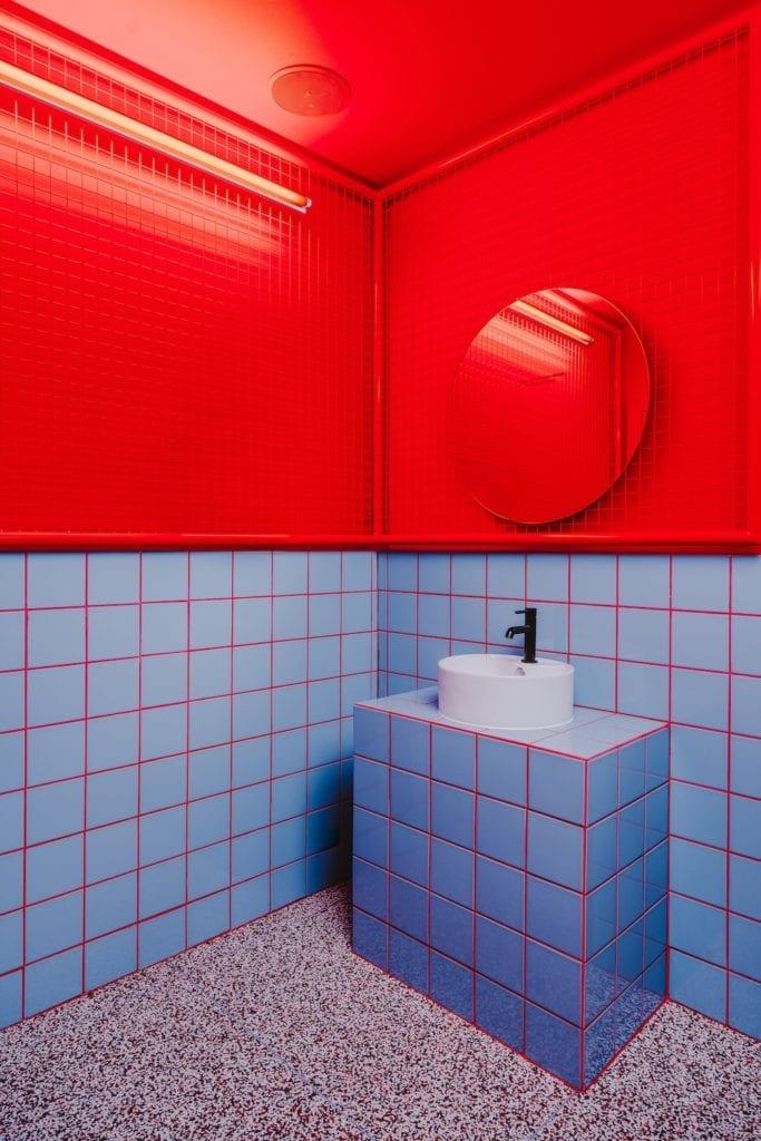 łazienka-w-restauracji-w-stylu-retro-niebieskie-kafelki-czerwona ściana-okrągłe-lustro