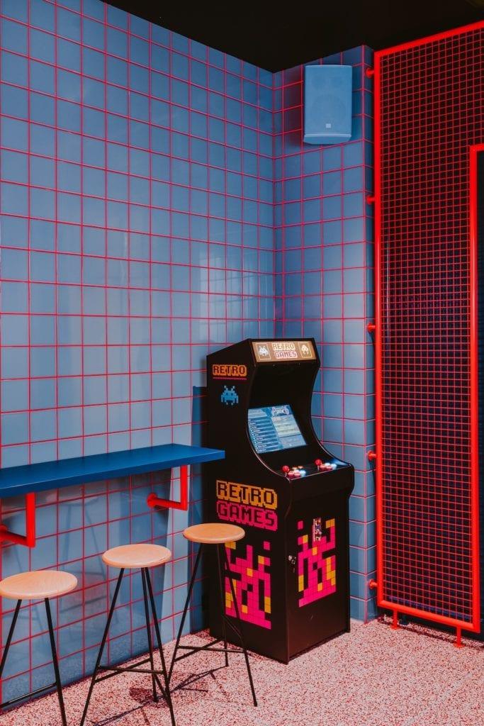 niebieskie-kafelki-czerwona-fuga-siatka-metalowa-przegroda-automat-z-retro-grami