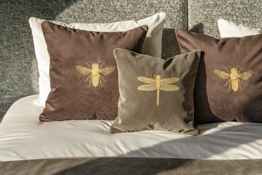 detale-sypialnia-poduszki-szare-aksamitne-na-łóżku-zdobione-rysumkiem-złotych-owadów