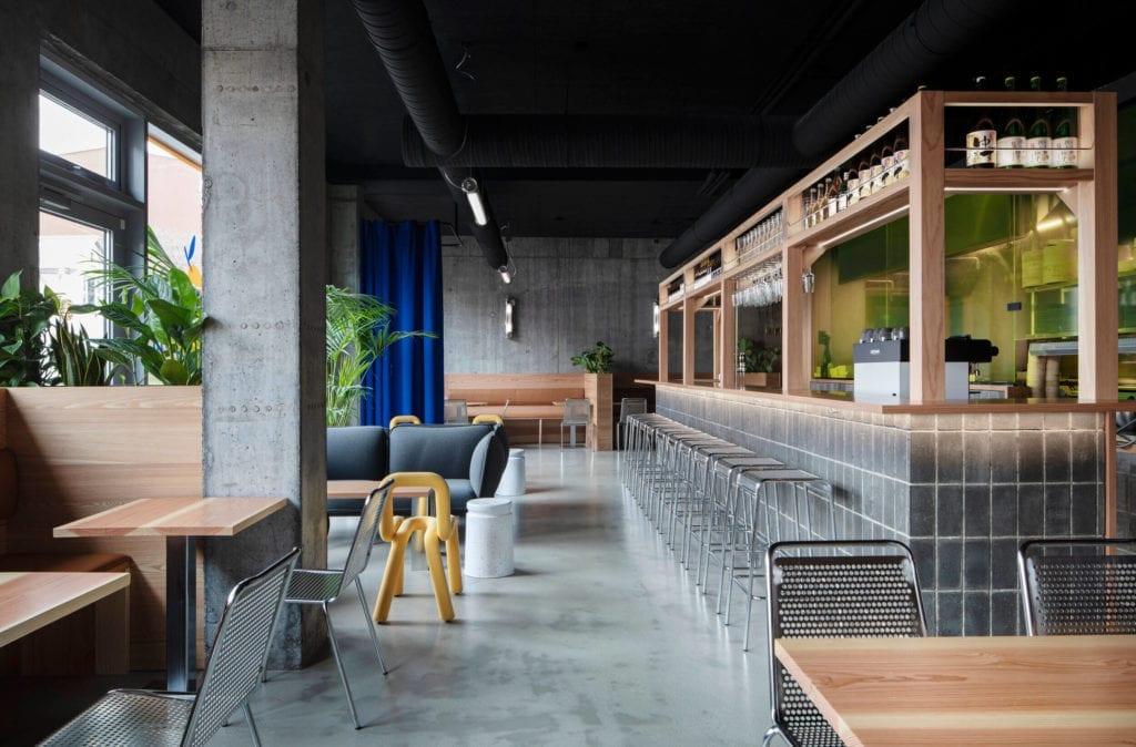 drewniany-bar-w-restauracji-japońskiej-piękne-wnętrze-inspiracje-niebieskie-zasłony-żółte-krzesło-betonowe-kafle-metalowe-siedziska