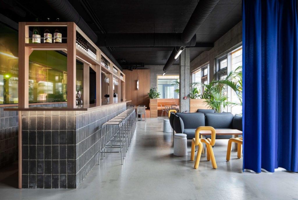 drewniany-bar-w-restauracji-japońskiej-piękne-wnętrze-inspiracje-niebieskie-zasłony-żółte-krzesło-betonowe-kafle