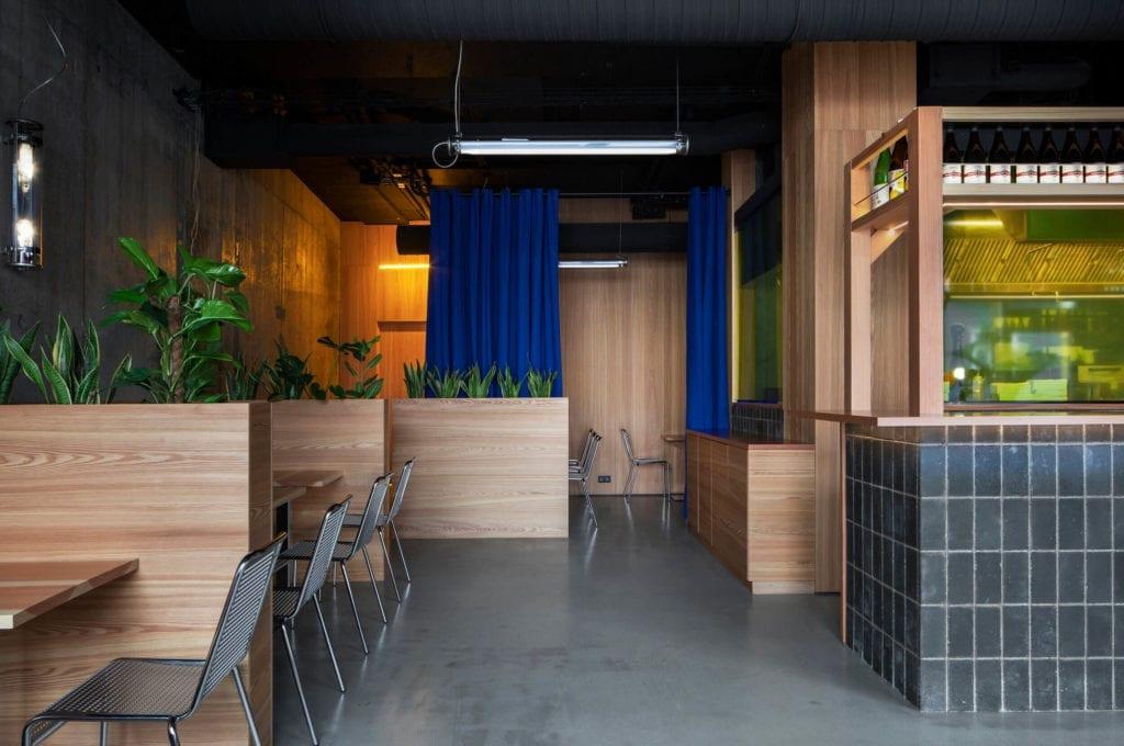 żywica-drewno-we-wnętrzu-restauracje-piękno-i-minimalizm-niebieskie-zasłony-metalowe-krzesła-rośliny