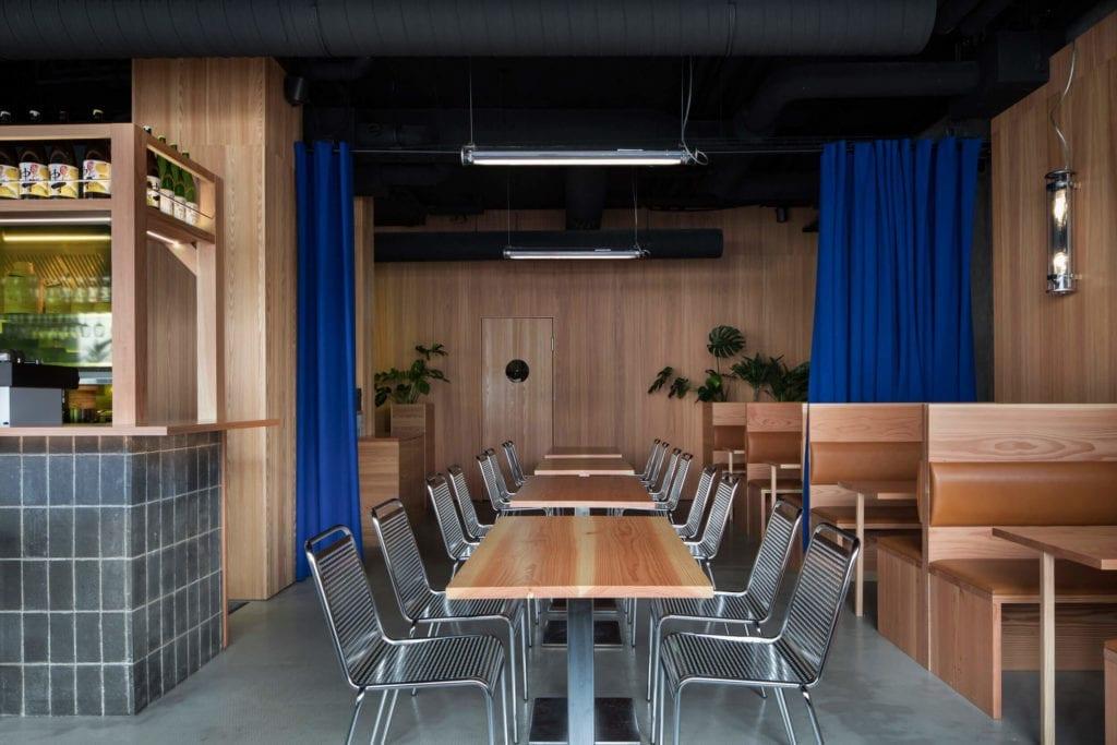 żywica-drewno-we-wnętrzu-restauracje-piękno-i-minimalizm-niebieskie-zasłony-metalowe-krzesła