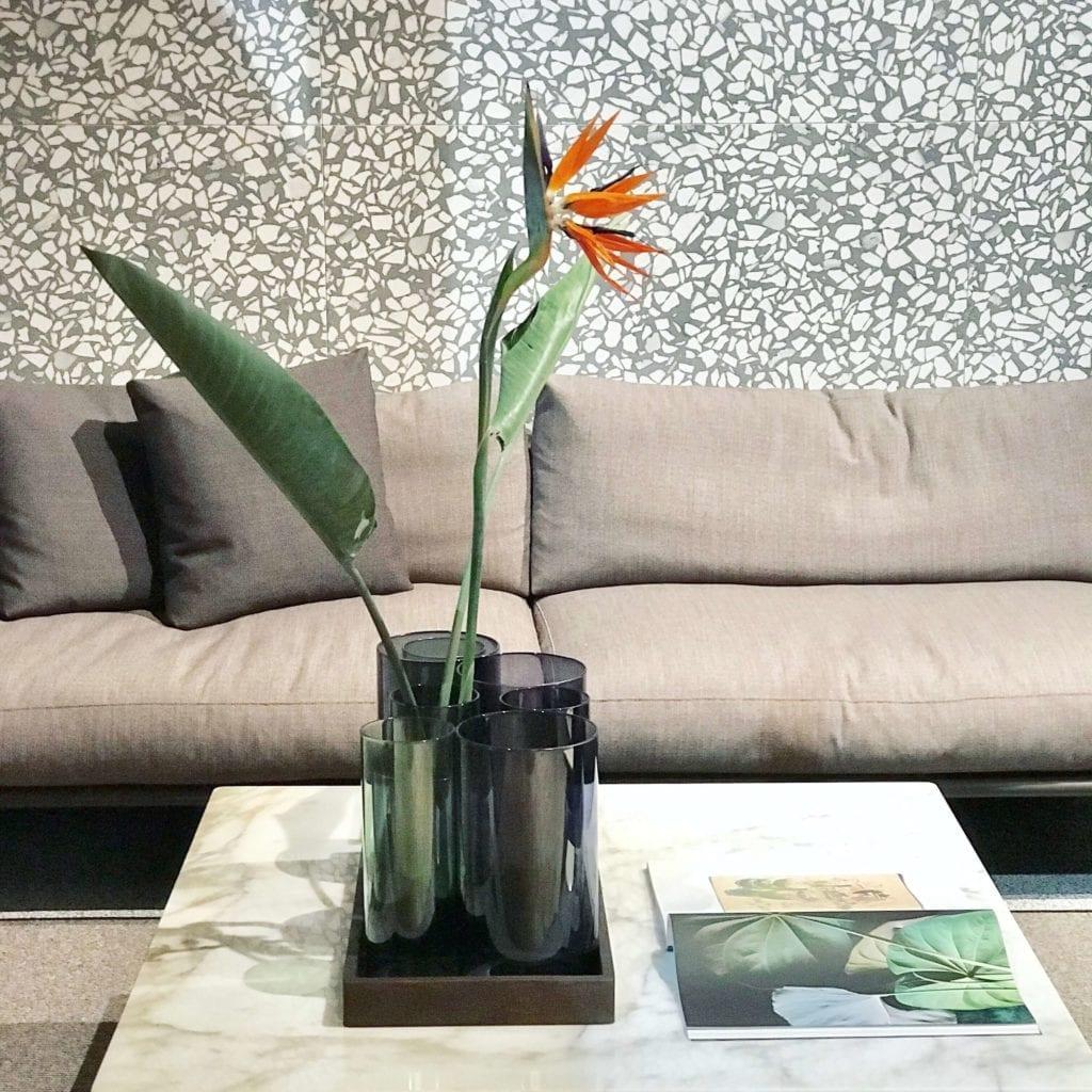 ściana-z-lastryko-co-to-jest-kanapa-inspiracje-salone-del-mobile-kwiat-na-stoliku-kawowym