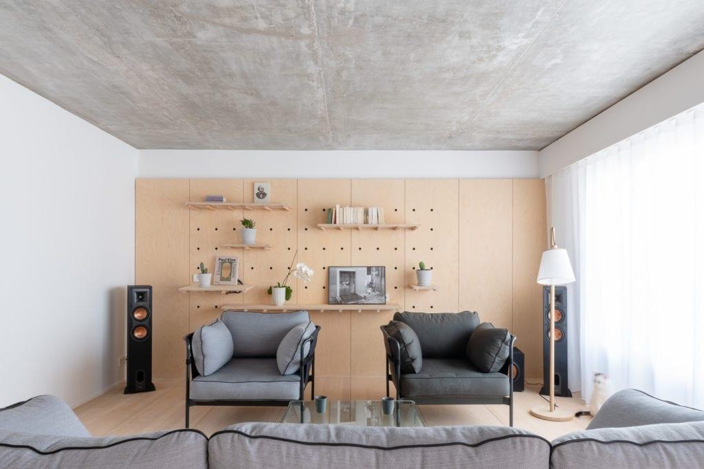 salon-kanapa-fotele-minimalizm-proste-białe-wnętrze-betonowy-sufit-białe-ściany-sklejka