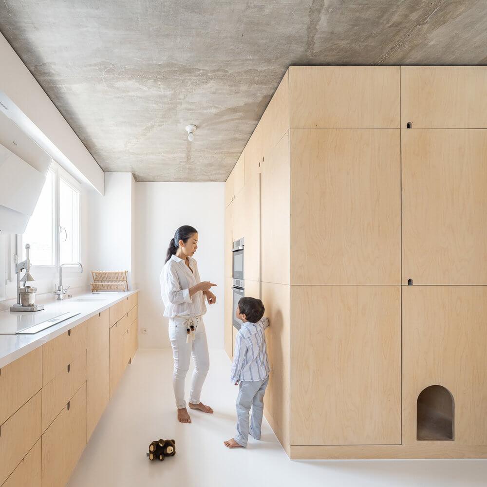 kuchnia-ze-sklejki-brzozowej-inpiracje-biel-wnętrze-nietypowe-mieszkanie-betonowy-sufit-miejsce-dla-kota