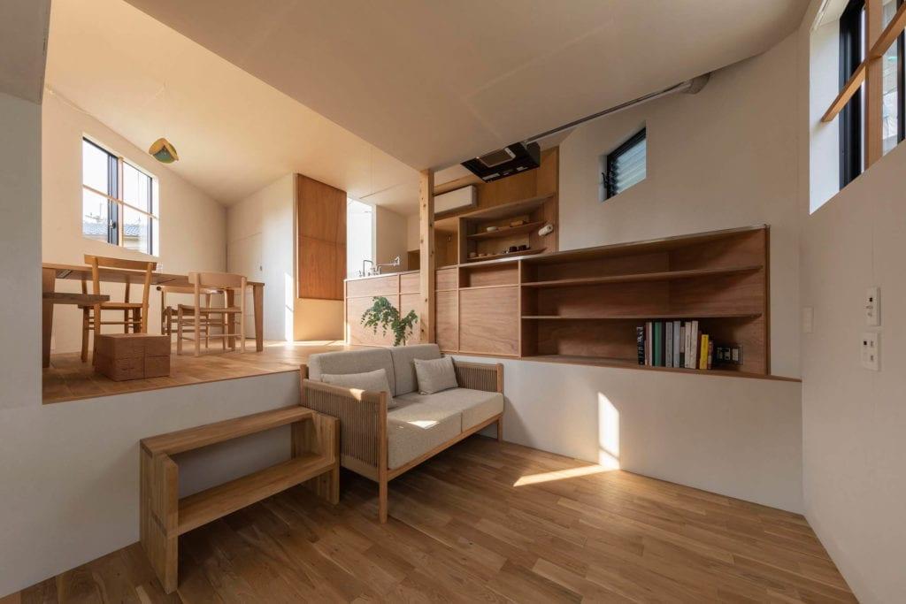 salon-w-domu-tto-architects-ciepłe-barwy-inspiracje-drewno-kanapa-półki