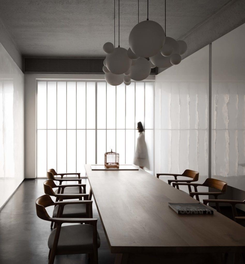 wnętrze-muzeum-inspiracje-białe-ściany-lampy-drewnainy-stół