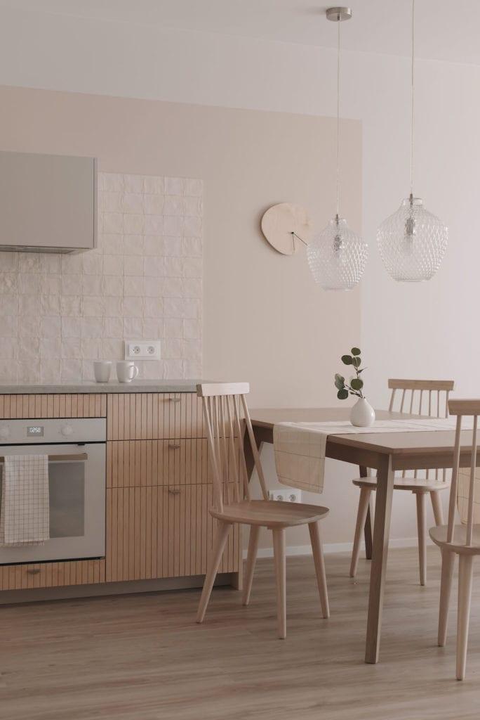 pastelowe-wnętrze-jadalnia-salon-z-kuchnią-inspiracje-stół-krzesła-lampy