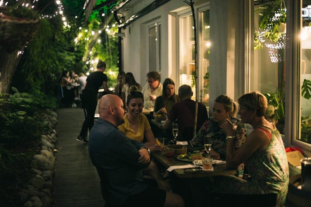 piękne-restauracje-warszawa-wnętrze-ogródek-inspiracje-drewno-stolik-lampki