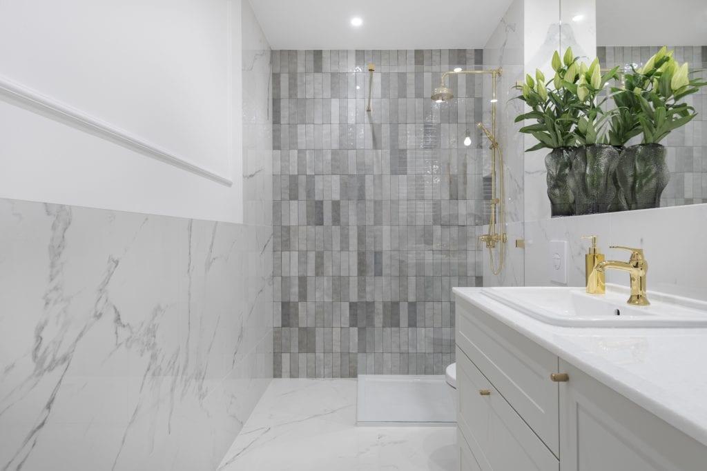 Jasna łazienka, duże lustro, złote dodatki, biały marmur, szafka na wymiar, sztukateria